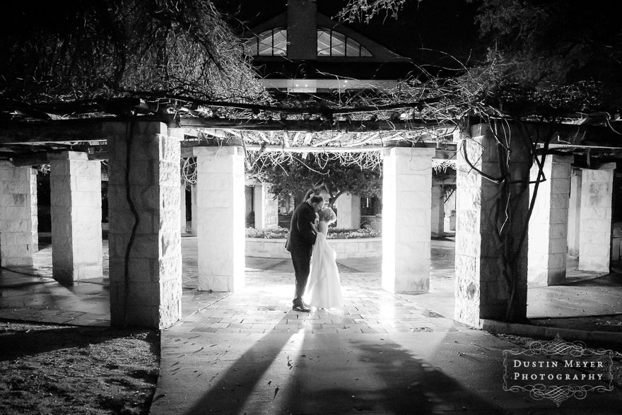 A creative photo of a wedding day portrait in black and white of a bride and groom at night with light shining from behind them.