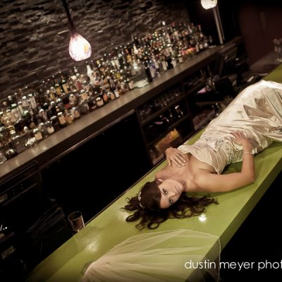 A bride lays across a green bar top in a dark lit bar room for her bridal portraits