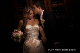A groom gives his bride a kiss as they sit on a couch in a winery while posing for a wedding photography workshop.