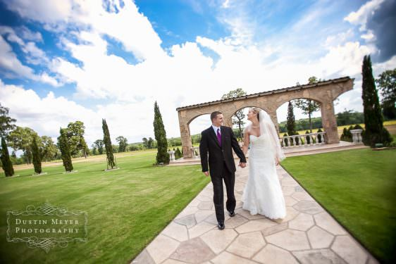 A bride and groom hold hands and smile at each other while walking down the aisle together in front of a stone arch with grass and trees and blue sky behind them for their wedding day portraits.