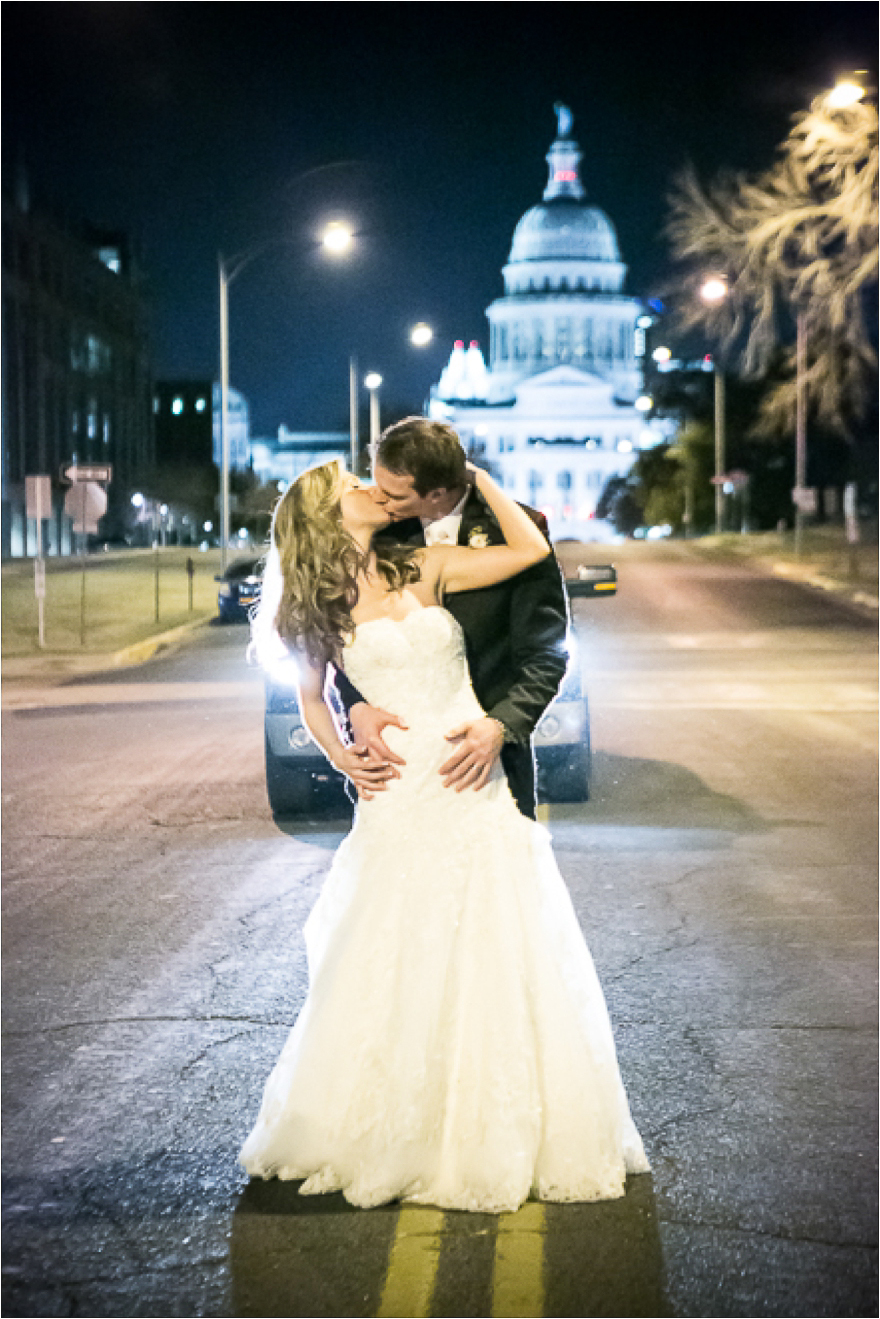 Brian and gloom pose for a gorgeous night time Austin skyline wedding day portrait in front of the Texas State Capitol building outside the Bob Bullock Texas State history Museum
