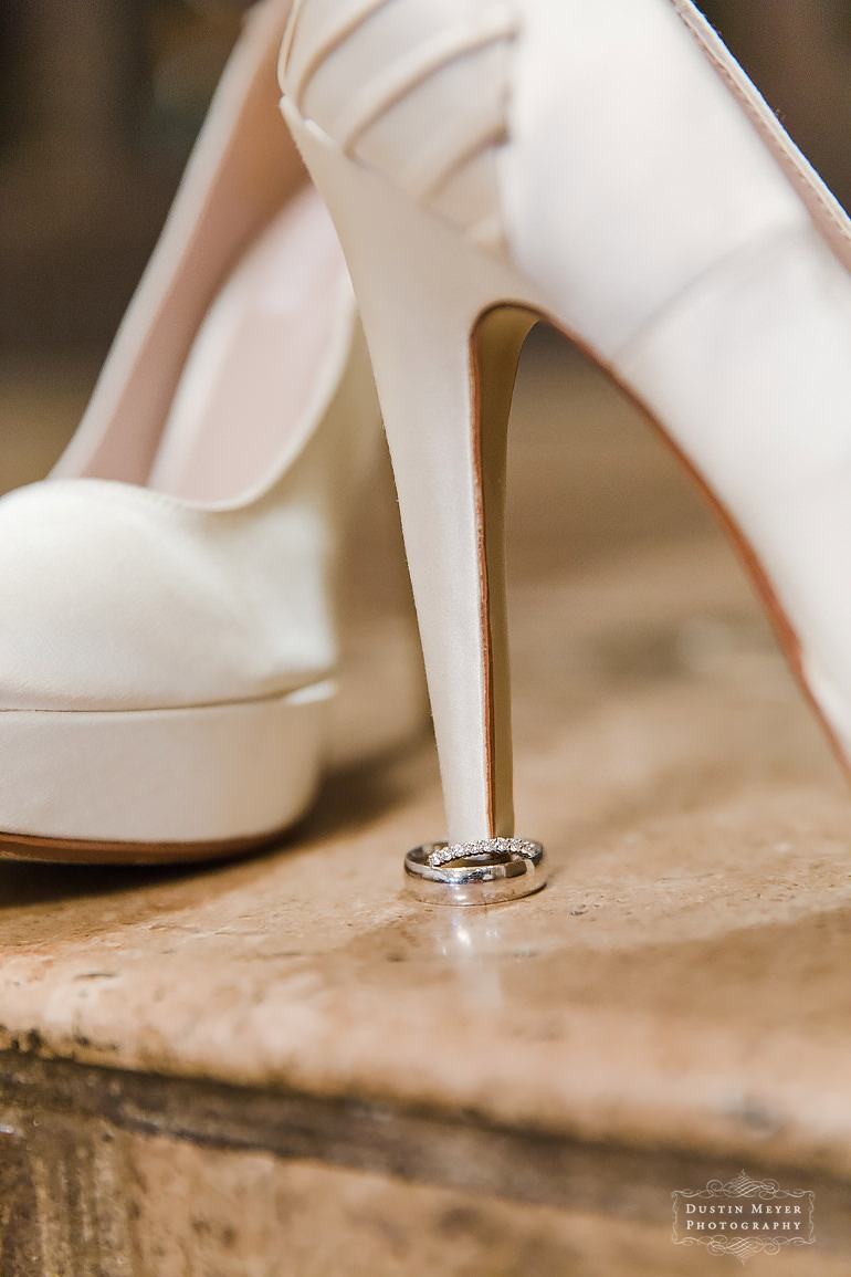 creative wedding rings shot with bridal wedding shoes