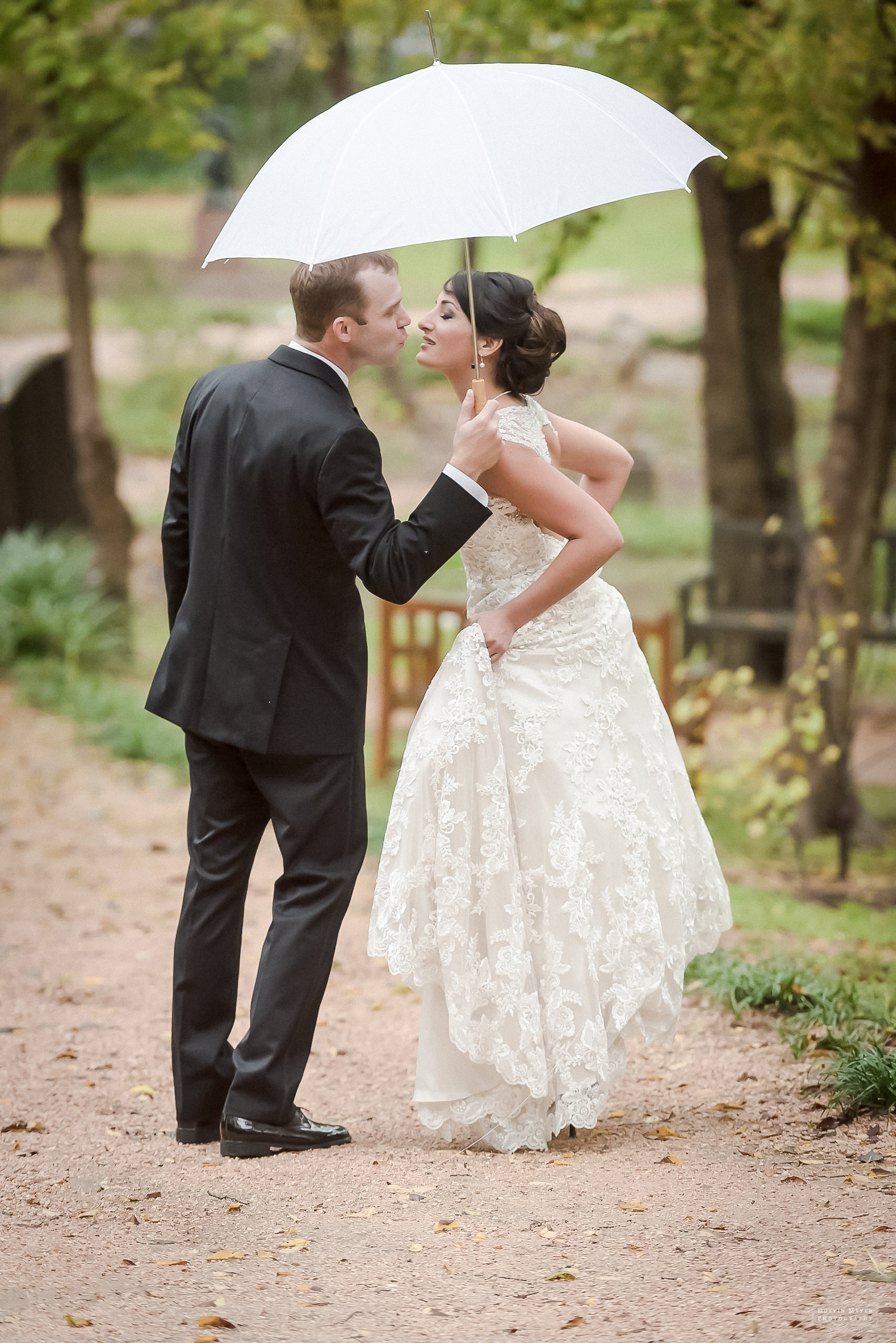 bride and groom kissing underneath umbrella