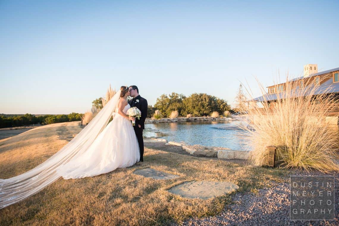 A stunning gorgeous wedding bride and groom next to a lake outdoors in a wedding dress and groom suit