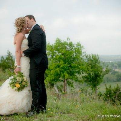 A bride wearing a Vera Wang wedding gown and her groom kissing at a hilltop wedding in the Texas hill country.